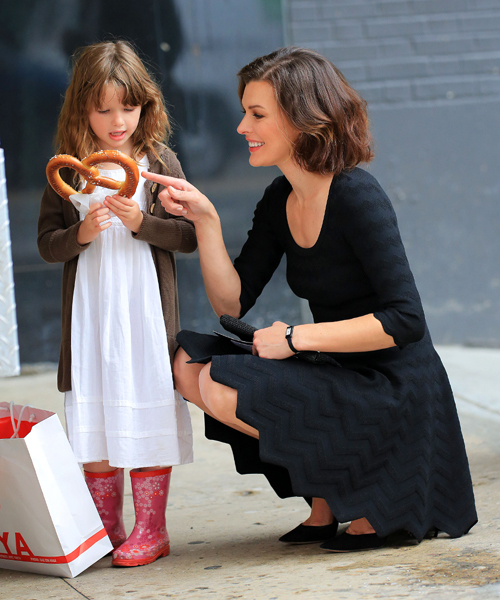 Milla Jovovich buys daughter Ever Gabo Anderson a pretzel in the Meatpacking District in NYC. Pictured: Milla Jovovich and Ever Gabo Anderson Ref: SPL391449  090512   Picture by: Jackson Lee / Splash News Splash News and Pictures Los Angeles:	310-821-2666 New York:	212-619-2666 London:	870-934-2666 photodesk@splashnews.com