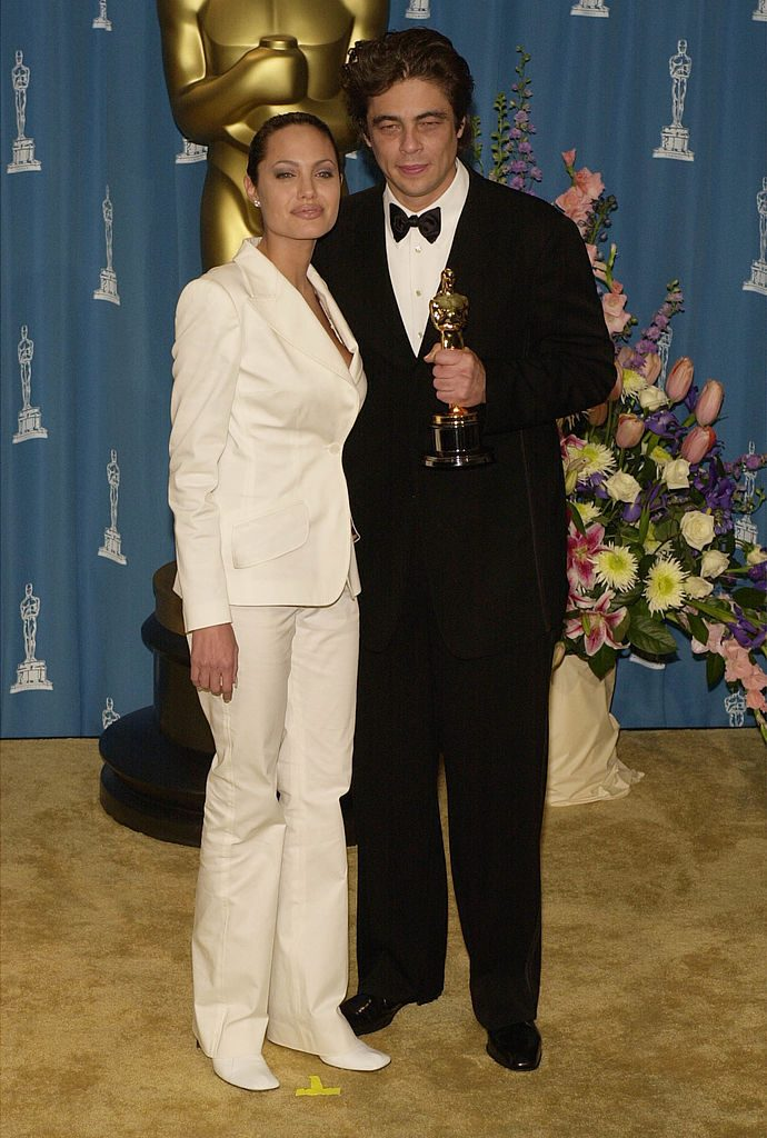386900 127: Best Supporting Actor Benicio Del Toro and actress Angelina Jolie pose for photographers during the 73rd Annual Academy Awards March 25, 2001 at the Shrine Auditorium in Los Angeles. Del Toro is wearing an Armani tuxedo and Jolie is wearing a Dolce and Gabbana outfit with hair by Paul DeArmas. (Photo by Chris Weeks/Getty Images