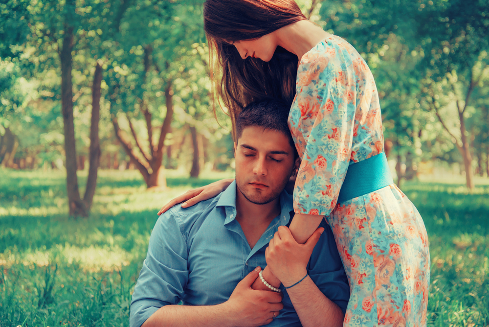 Young loving couple resting in summer park. Woman hugging a man, tender scene. Image with instagram color effect