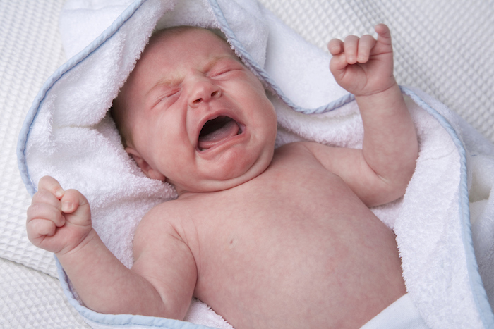 A crying newborn in a white towel.