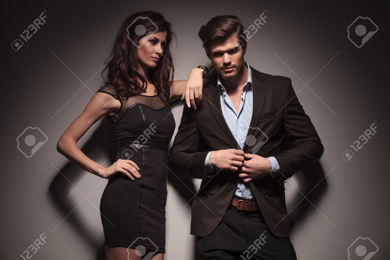 32001428-picture-of-a-elegant-fashion-couple-the-man-is-unbuttoning-his-jacket-while-the-woman-is-looking-at-stock-photo