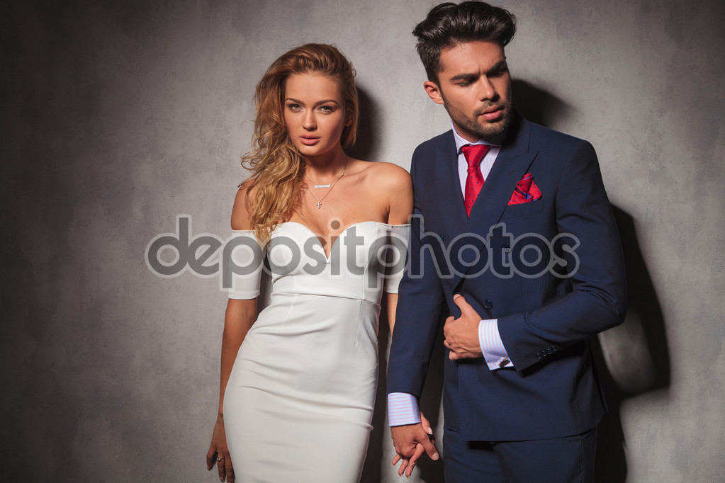 macho fashion elegant man holding his lover by her hand